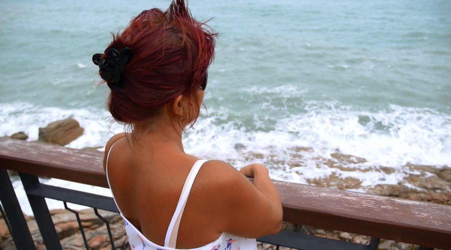 A widow stands by herself overlooking a beach and watching the ocean.